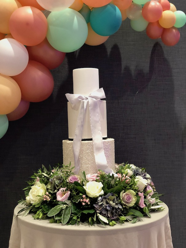 Organic balloon display over wedding cake