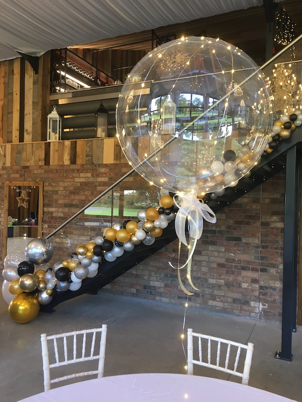 Organic balloon staircase feature along with clear LED balloons